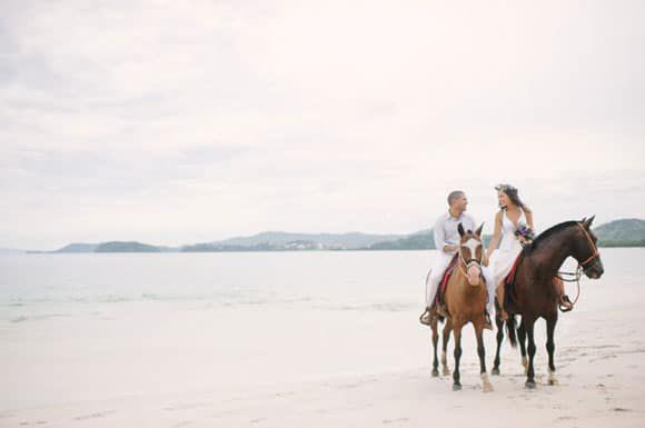 Newlyweds on the beach with horses