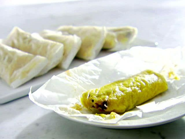 A white plate with a bean and cheese tamale. There are more wrapped bean and cheese tamales on a platter in the background.
