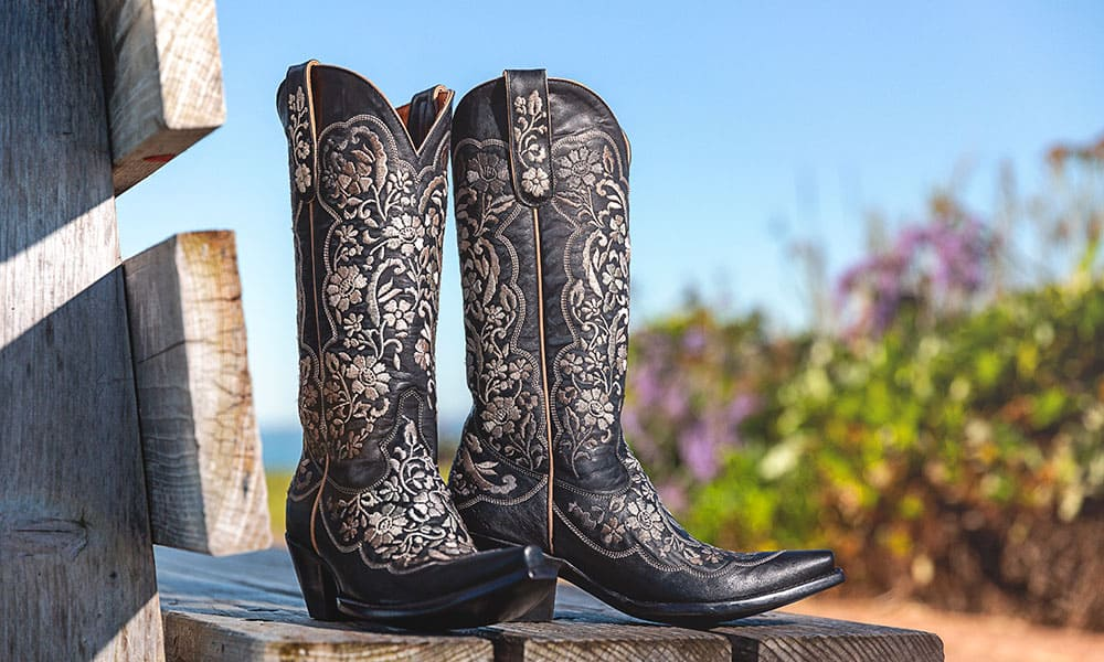 black embroidered boots on a wood fence in front of a desert background