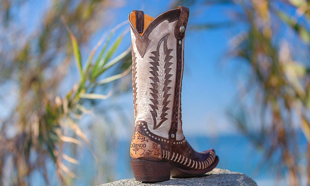 exotic brown and white boot in front of blue sky with palm trees in the background