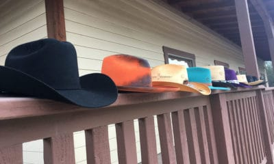 hats lined up on a fence