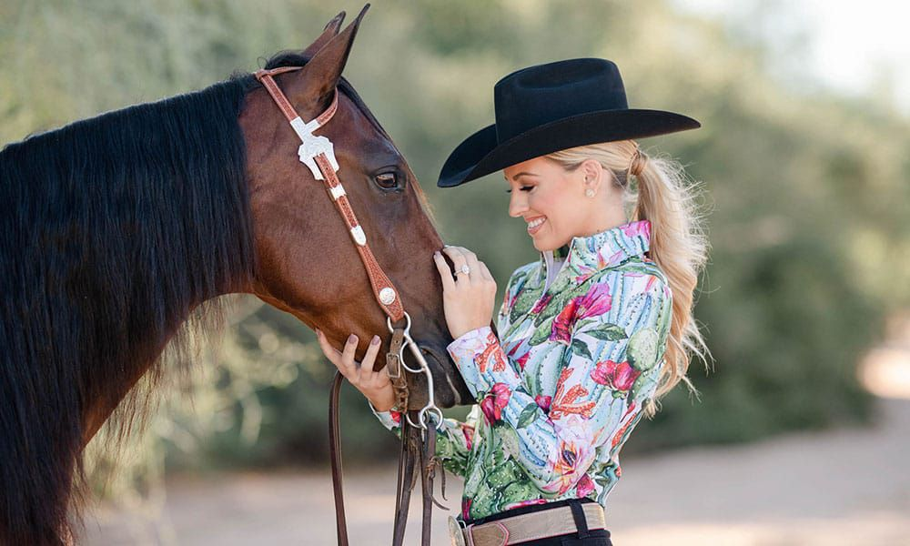 blouse with cactus and flowers on women who is petting a horse