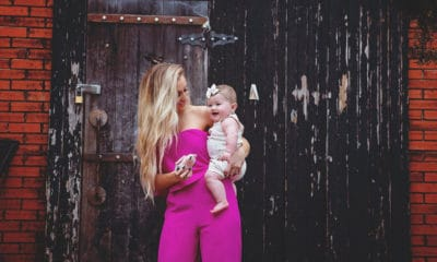woman in pink jumper, holding baby, in front of a wall