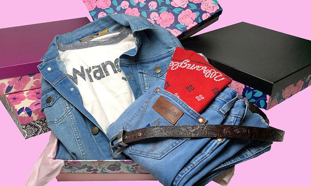 denim jacket, jeans, red bandana, belt, white wrangler t-shirt, on a pink background in a box