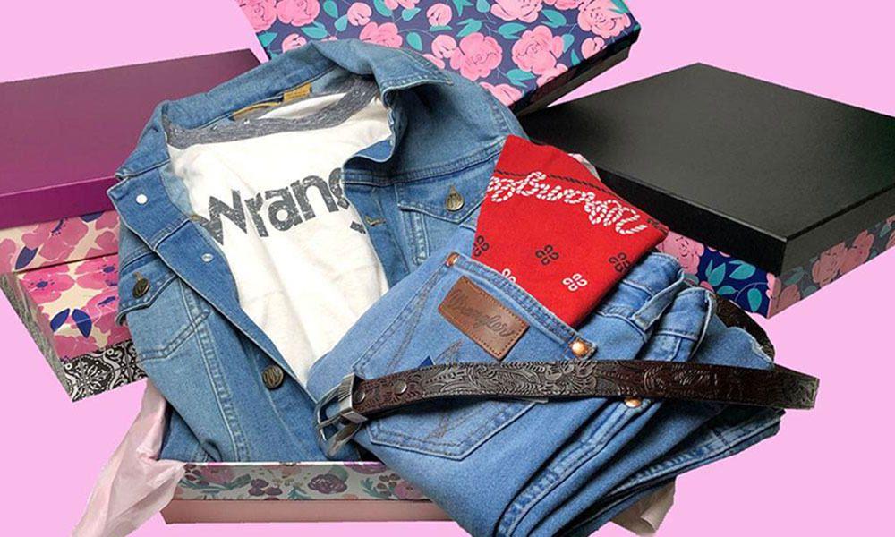 denim jacket, jeans, red bandana, belt, white wrangler t-shirt, on a pink background in a box