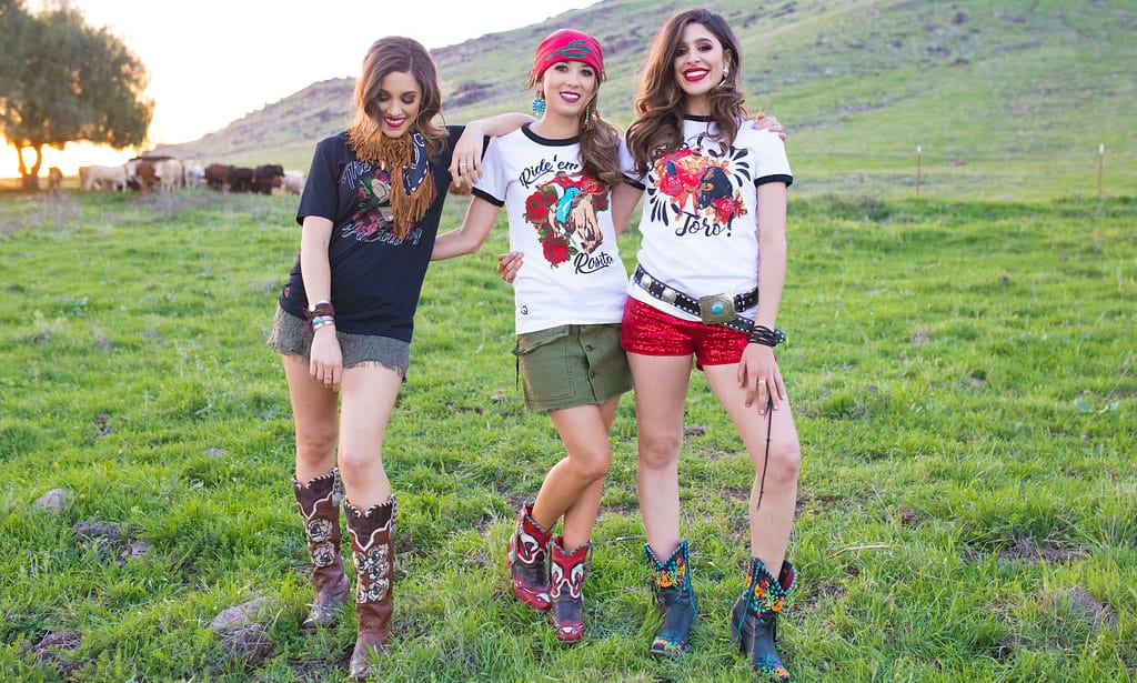 three girls wearing rodeo quincy clothes, from boots, to tee shirts to shorts and belts
