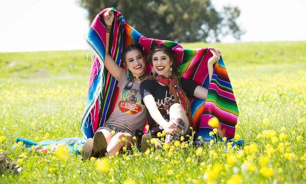 girls in a field with flowers and a serape blanket wearing rodeo qunicy tees