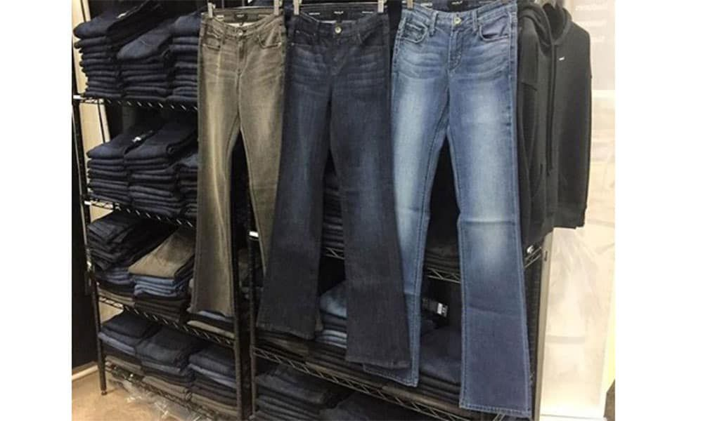 three pairs of riding jeans hanging on a rack in front of other jeans