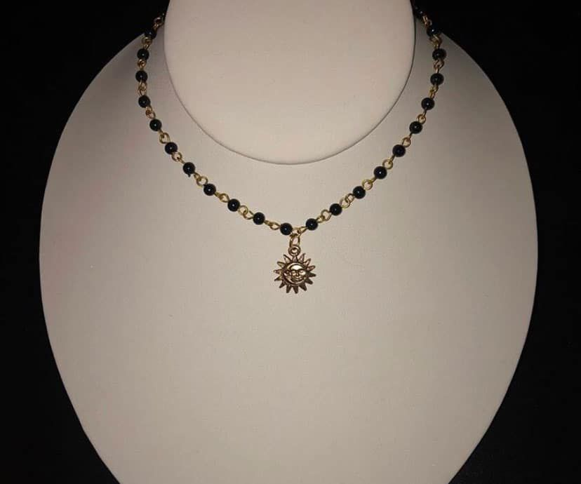 black eclipse necklace with sun charm