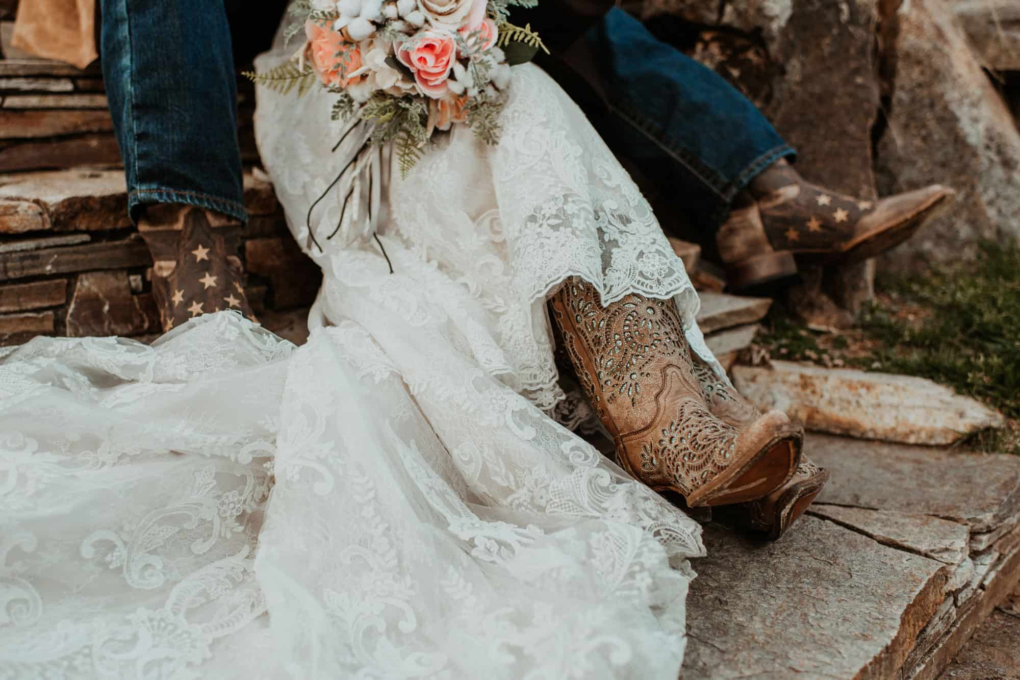 Corral wedding boots on a bride in a wedding dress holding flowers