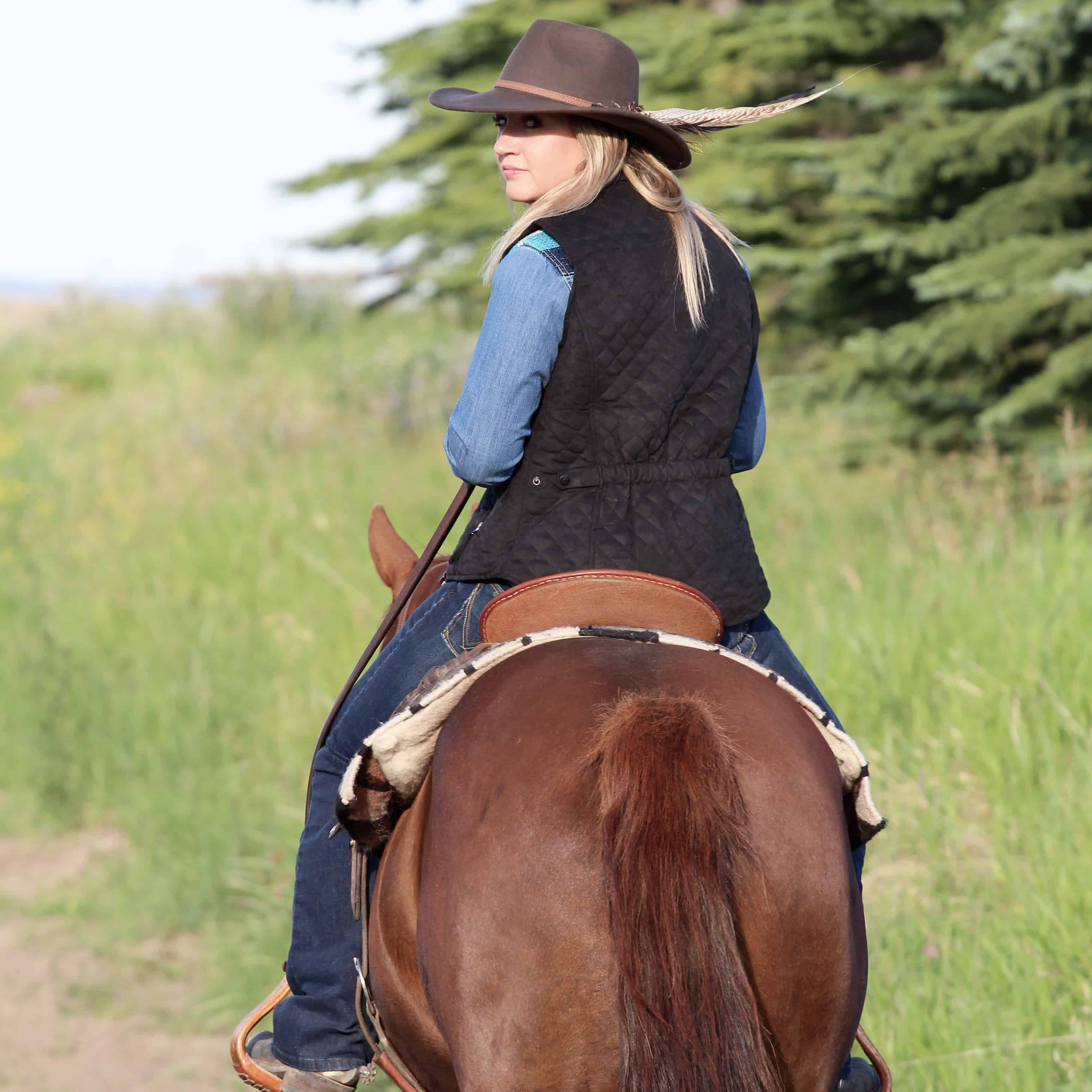 vest from outback trading co on a girl riding a horse with a spring hat on